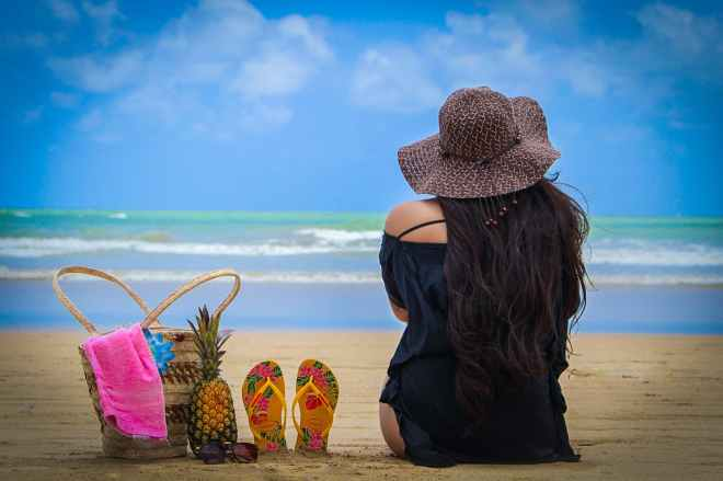 photo of woman sitting on beach