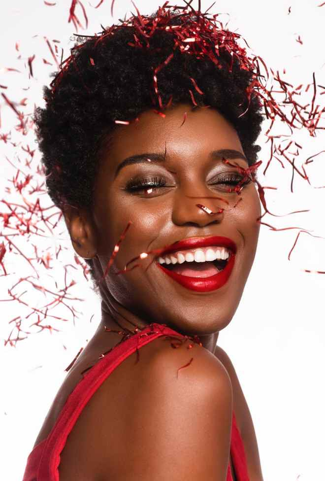 close up photo of smiling woman with her eyes closed posing as confetti drops down her face