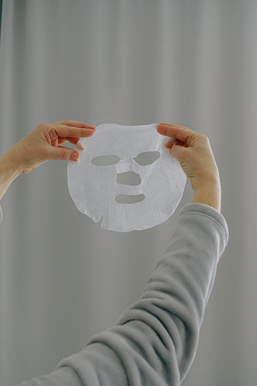 crop woman with sheet face mask