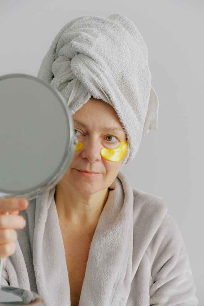 woman in white bath robe holding round mirror